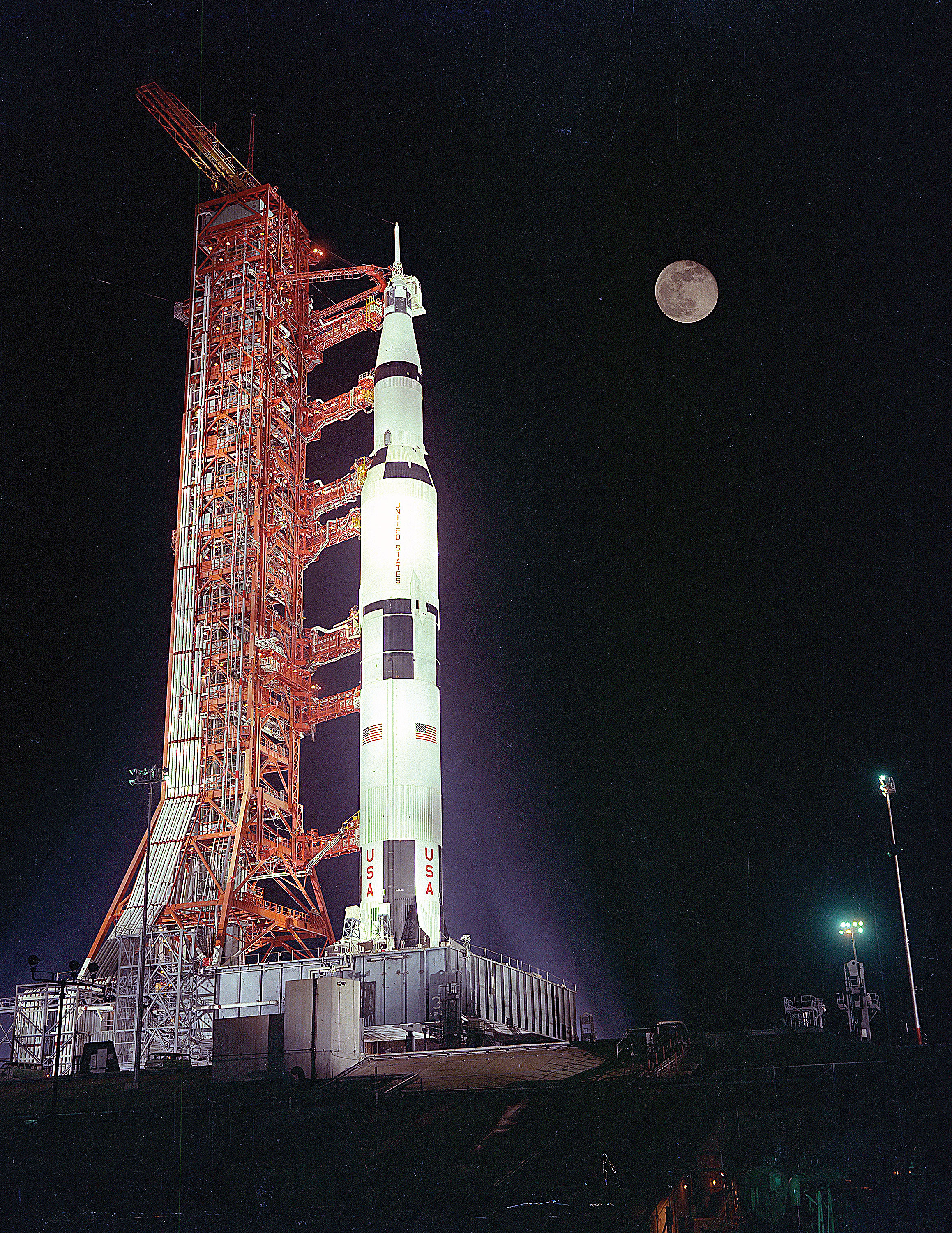 The Apollo 17 rocket is shown at night with the Moon in the background. Credit: NASA via J.L. Pickering/Retro Space Images