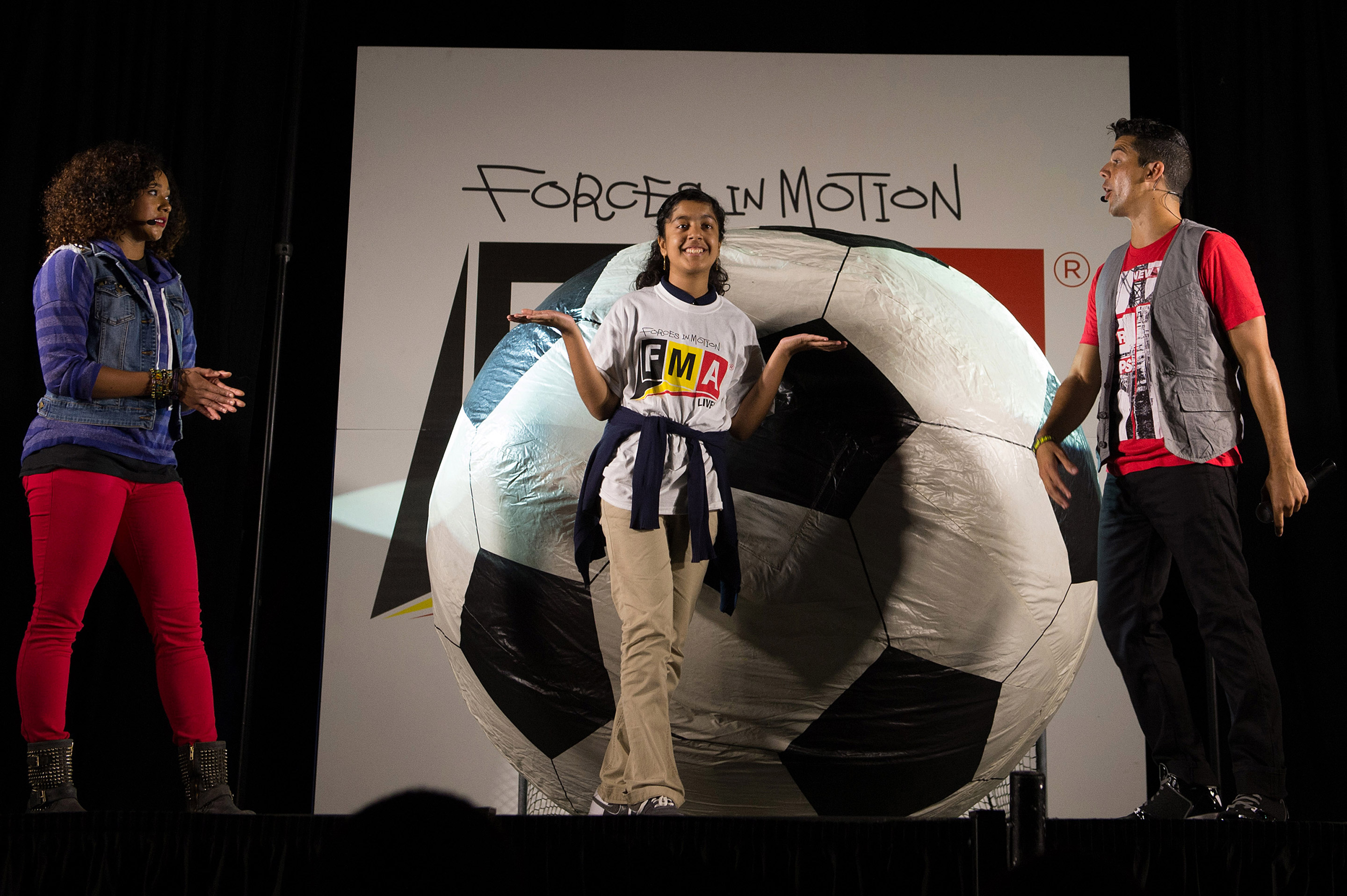 """With the help of a student participant, """"FMA Live!"""" crew members explain Newton's second law of motion during the same performance. """"FMA Live!"""" is a program sponsored by NASA and Honeywell that teaches Newton's three laws of motion mixed with dance and music. Image: NASA/Jay Westcott"""