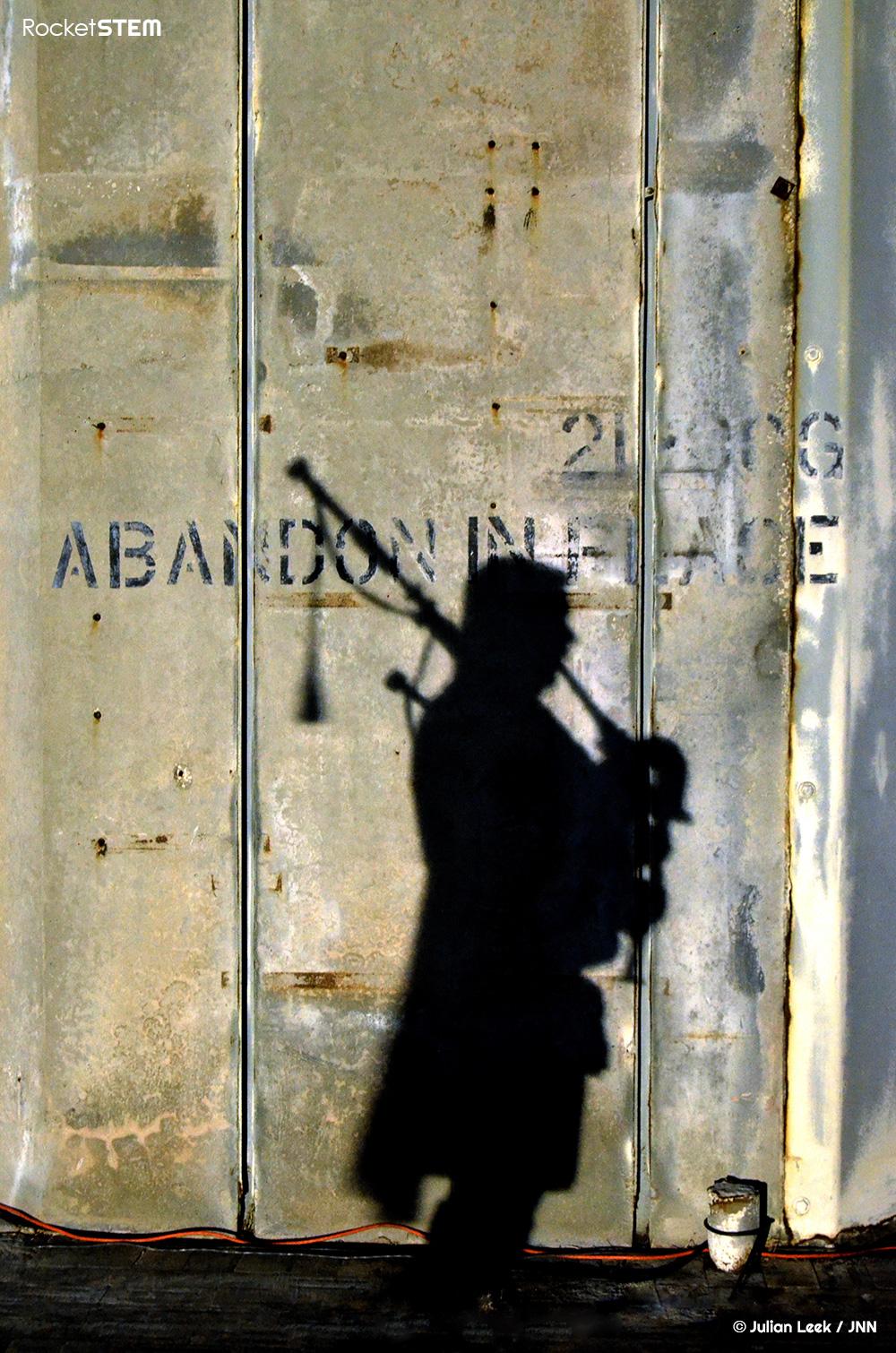 Silohuette of a bagpiper against the LC-34 concrete launch pedestal. Photo: Julian Leek/JNN