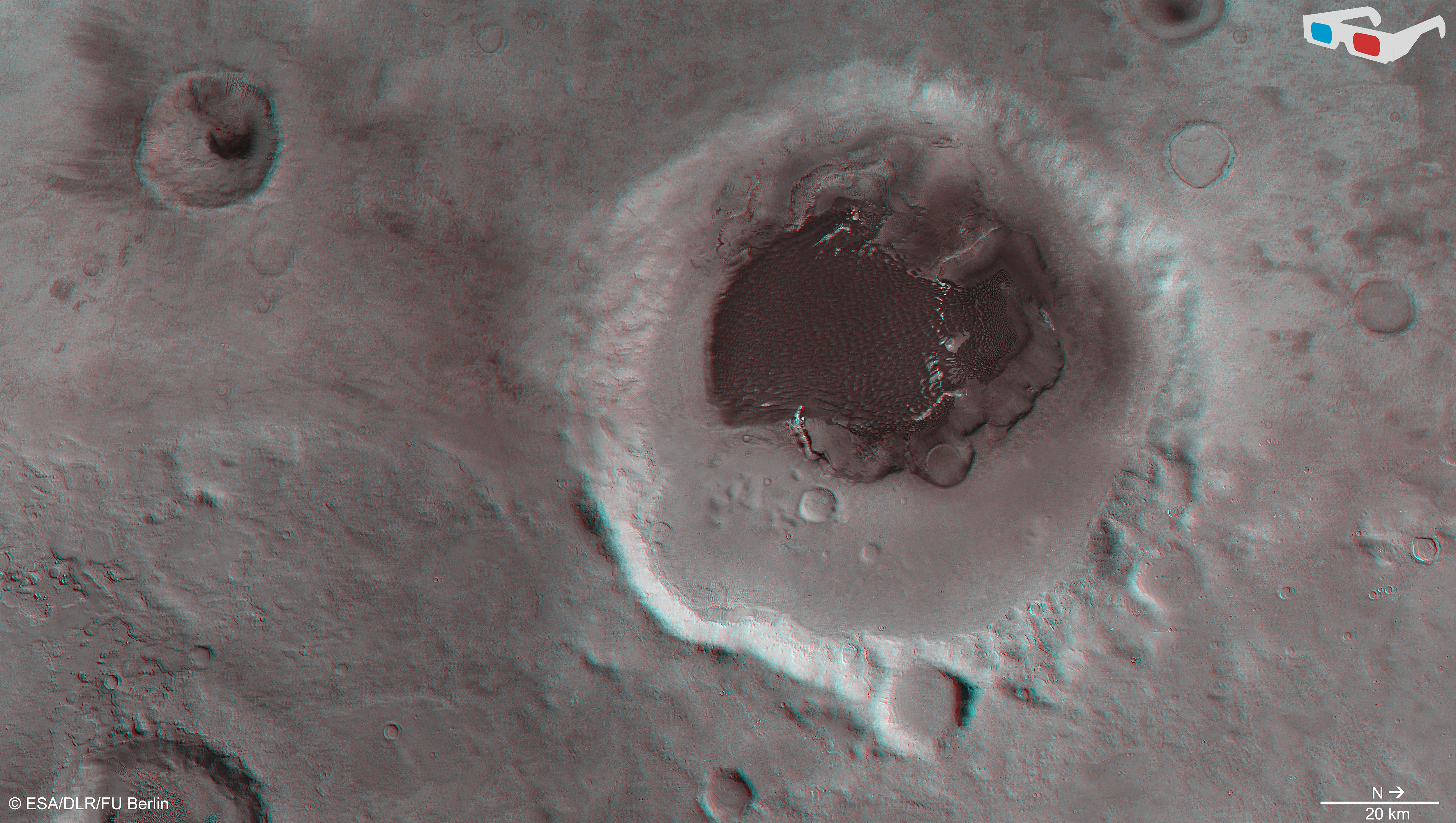 Data from the nadir channel and one stereo channel of the High Resolution Stereo Camera on Mars Express have been combined to produce this anaglyph 3D image, which can be viewed using stereoscopic glasses with red–green or red–blue filters.The image focuses on Rabe crater and its intricate dune field, material that has been shaped by prevailing winds. The image was created using data acquired with the High Resolution Stereo Camera on Mars Express on 7 December 2005 (orbit 2441) and 9 January 2014 (orbit 12736).Credit: ESA/DLR/FU Berlin