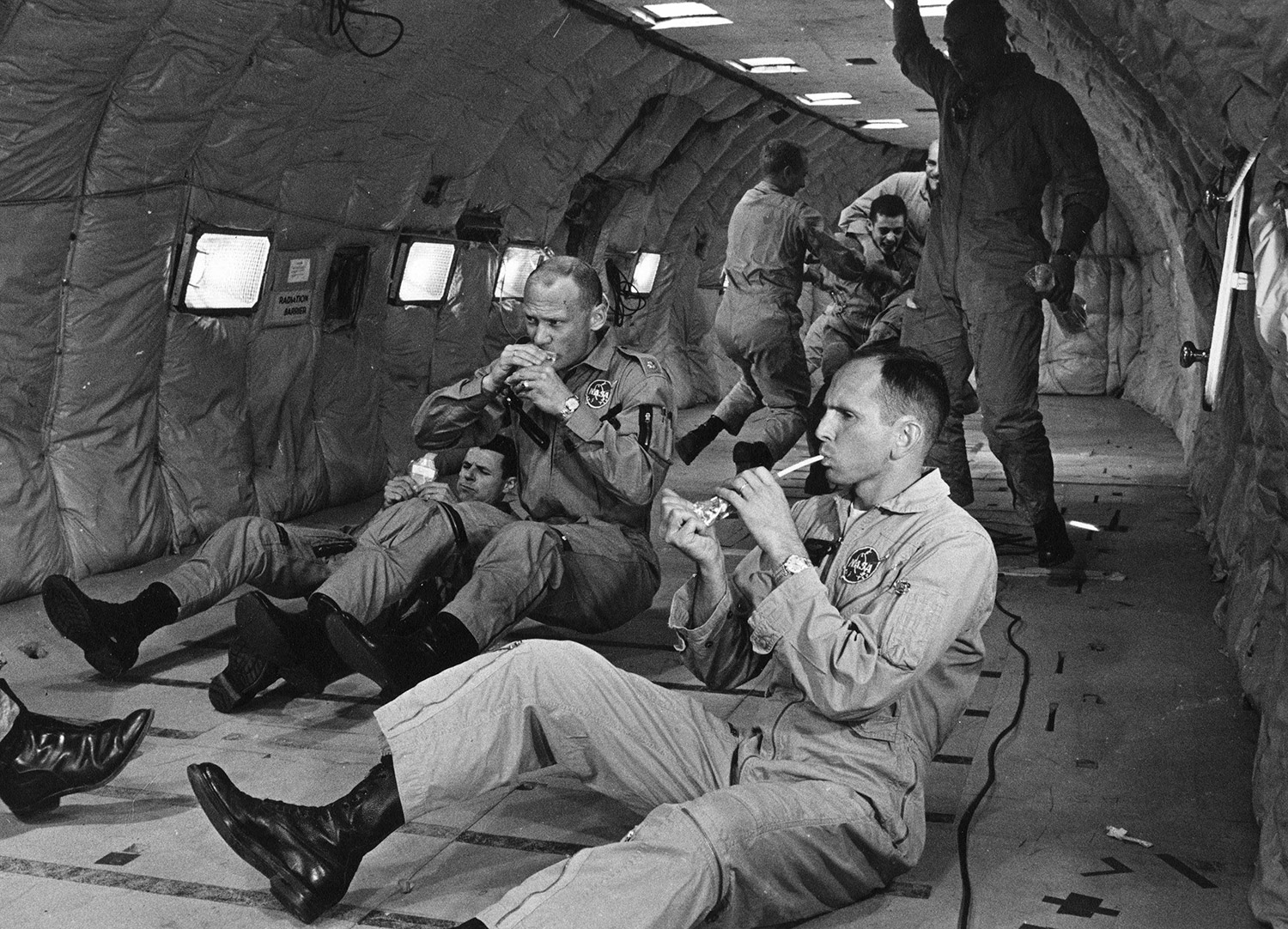 While flying parabolic arcs to simulate weightlessness aboard a KC-135 at Wright-Patterson AFB in August of 1964, Buzz Aldrin attempts to consume a container of space food. Fellow NASA astronauts Charlie Bassett (left) and Ted Freeman (right) are also trying to eat the specially prepared food. Credit: NASA via Retro Space Images