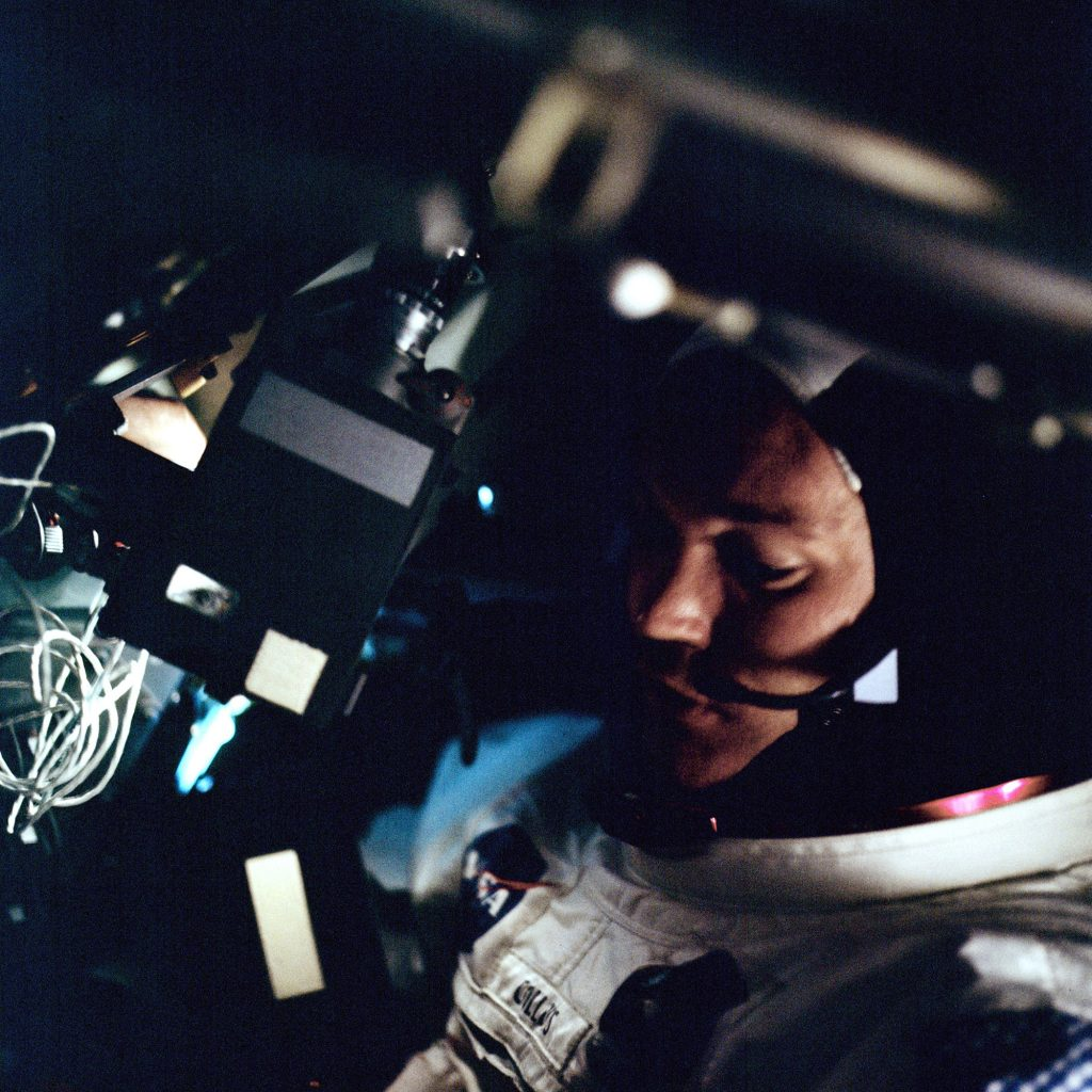 Michael Collins aboard the Apollo 11 spacecraft during the trip to the Moon. As the Command Module Pilot, Collins stayed in orbit around the Moon, while Neil Armstrong and Aldrin descended to the surface and became the first men to walk on the Moon.