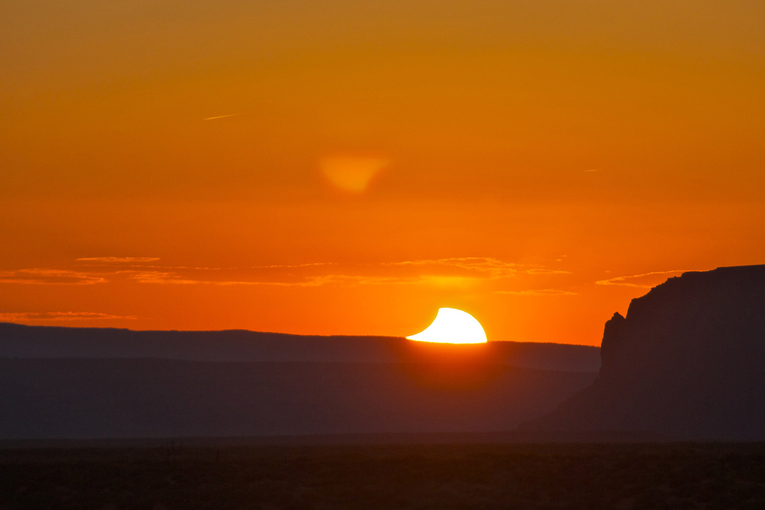 An eclipse of the Sun at sunset over Monument Valley, Utah shows the Moon gradually moving off revealing the surface of the Sun. Credit: Mike Barrett