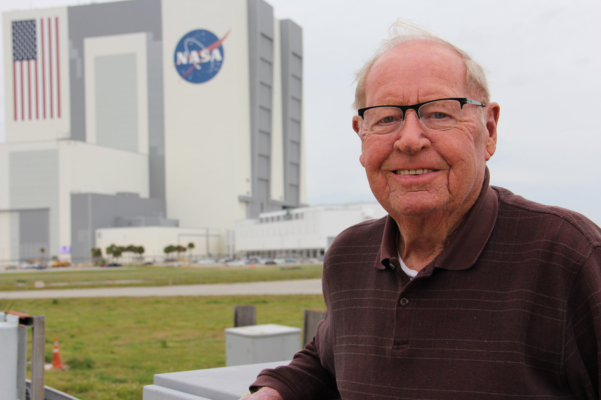 Jack King stands outside the KSC Press Center with the VAB in the background. Credit: Nicole Solomon