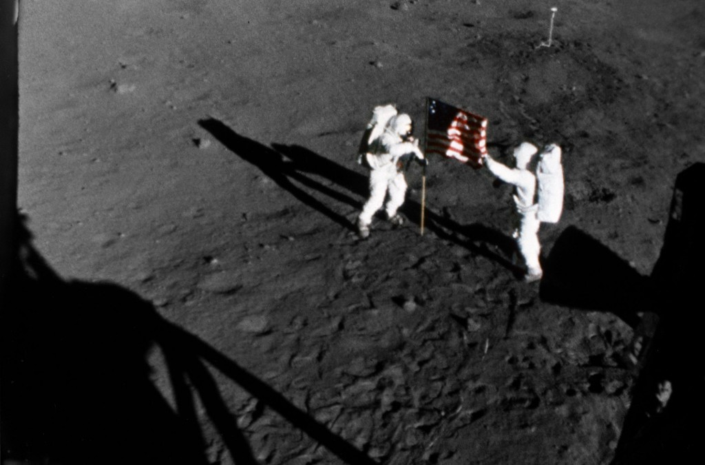 Armstrong and Aldrin deploy the American flag outside near the Lunar Module at Tranquility Base in the Sea of Tranquility on July 20, 1969.