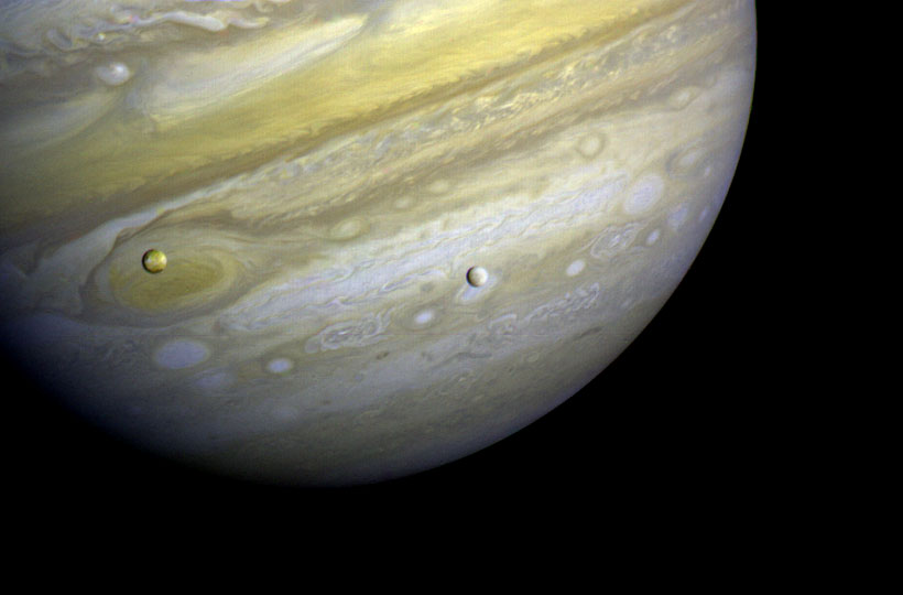 Voyager 1 took this photo of Jupiter and two of its satellites (Io, left, and Europa) on Feb. 13, 1979. Io is about 350,000 kilometers (220,000 miles) above Jupiter's Great Red Spot; Europa is about 600,000 kilometers (375,000 miles) above Jupiter's clouds. Credit: NASA/JPL