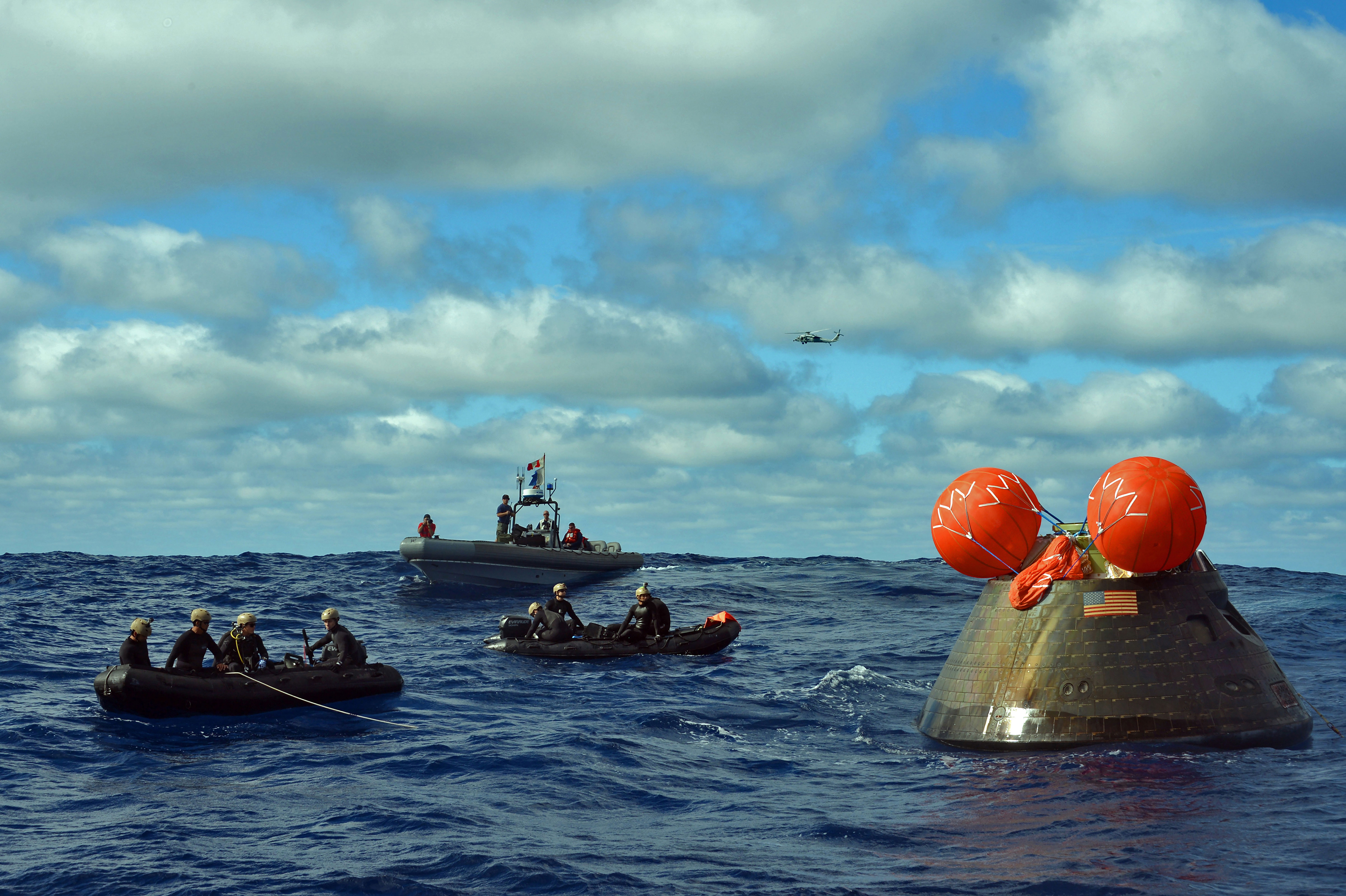 Sailors from the amphibious transport dock, USS Anchorage, and Navy Divers attach a line to the Orion Crew Module. Credit: U.S. Navy/Corey Green