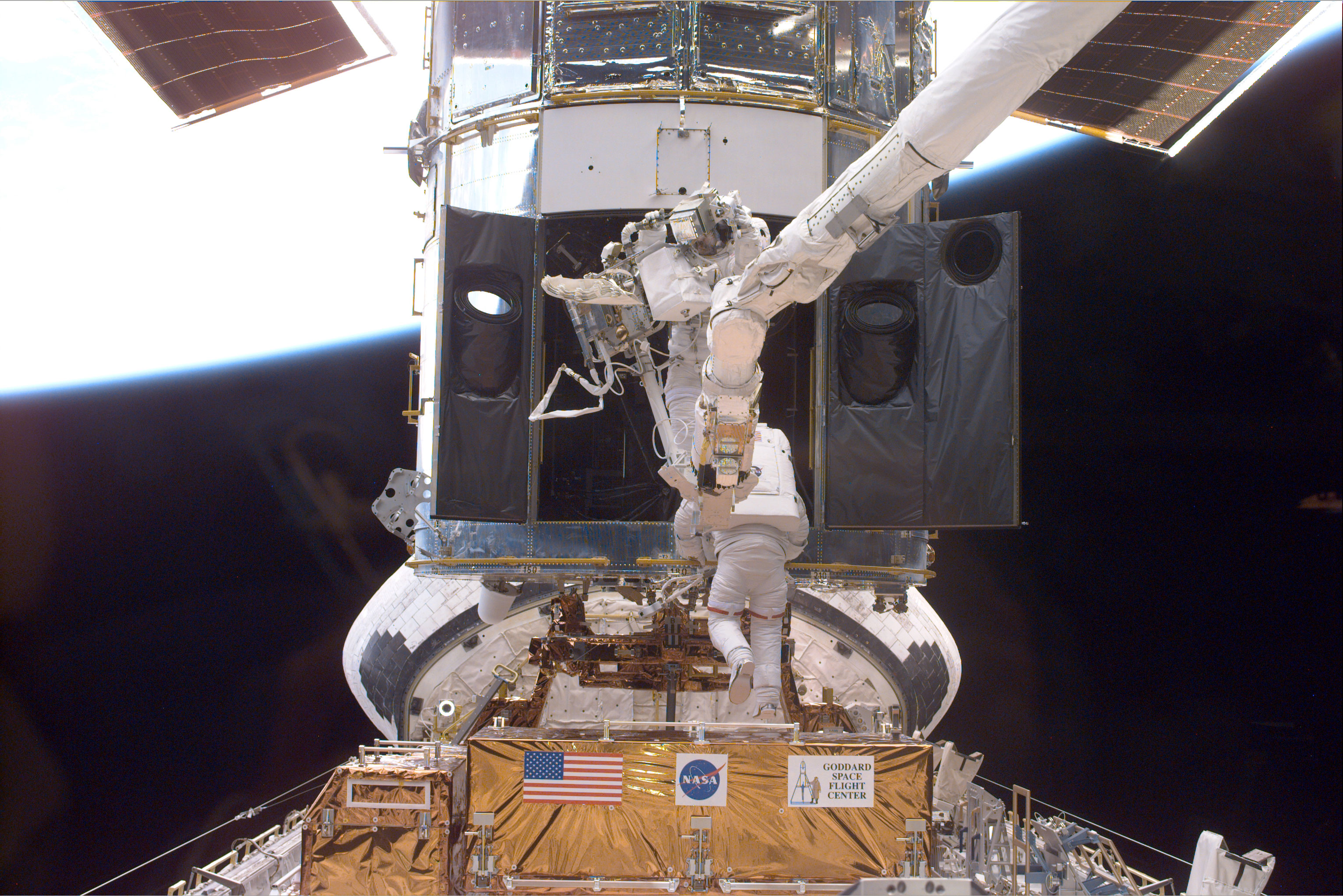 Payload Commander Steven L. Smith (bottom), and Mission Specialist John M. Grunsfeld, perform servicing tasks on the temporarily-captured Hubble Space Telescope. Grunsfeld is on a foot restraint connected to Discovery's RMS robot arm. Smith, making his second servicing visit to HST, is using handrails on the telescope. Credit: NASA