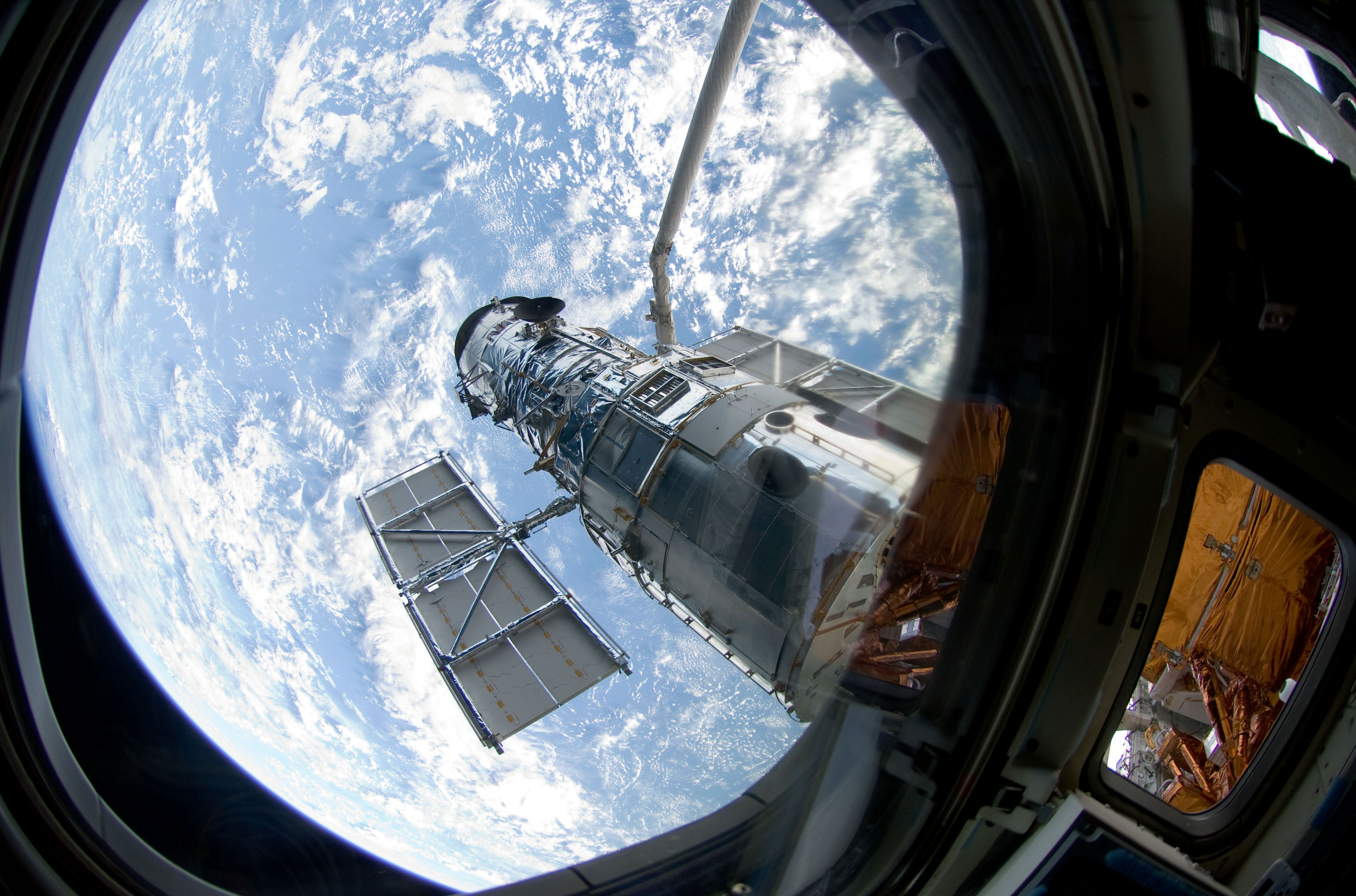 An STS-125 crewmember onboard Atlantis snapped a still photo of the Hubble Space Telescope following grapple of the giant observatory by the shuttle's Canadian-built remote manipulator system. Credit: NASA