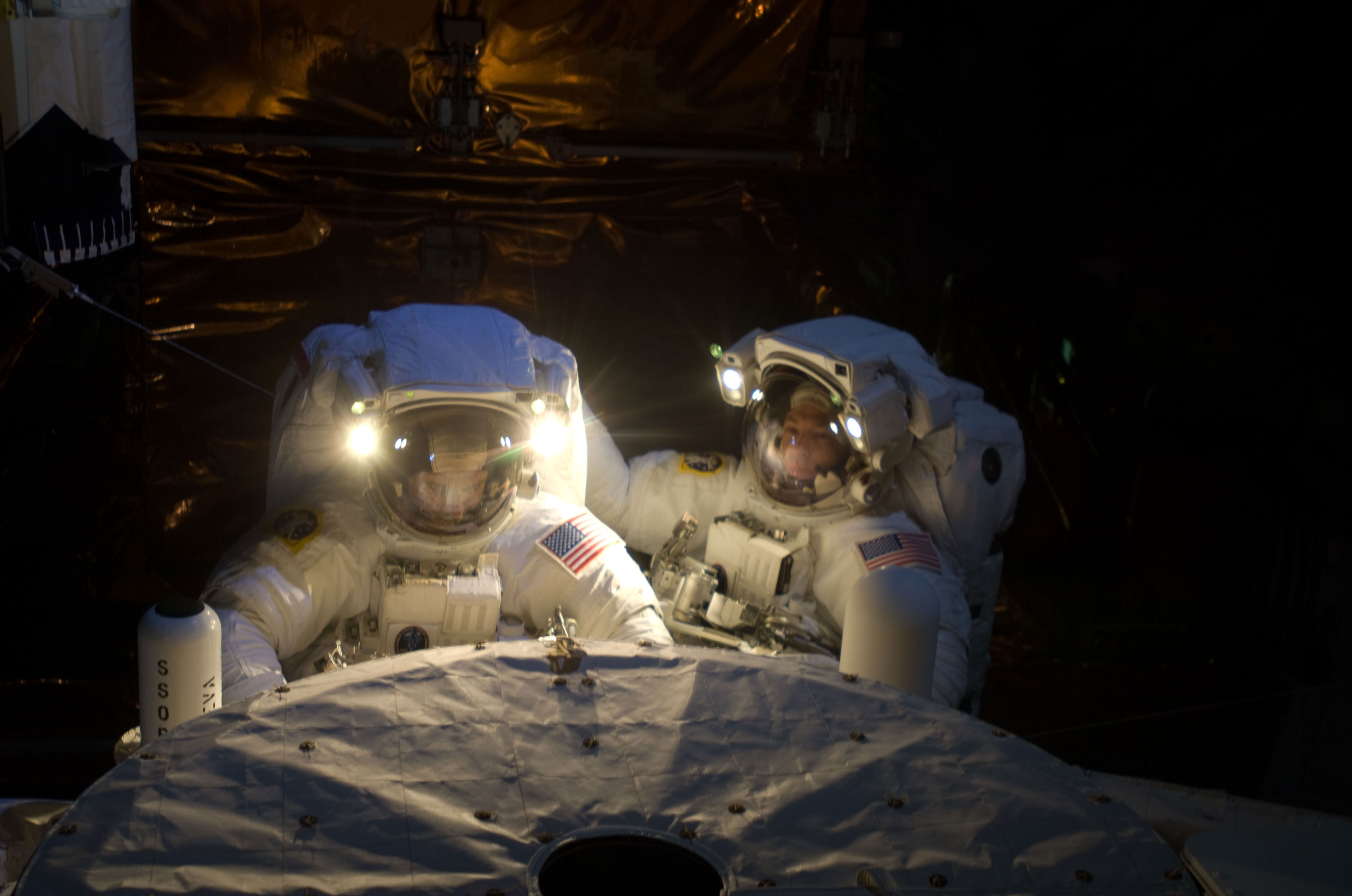 Astronauts John Grunsfeld (left) and Andrew Feustel, both STS-125 mission specialists, participate in the mission's fifth and final ever session of extravehicular activity (EVA) to repair and upgrade the Hubble Space Telescope. During the seven-hour and two-minute spacewalk, Grunsfeld and Feustel installed a battery group replacement, removed and replaced a Fine Guidance Sensor and three thermal blankets (NOBL) protecting Hubble's electronics. Credit: NASA