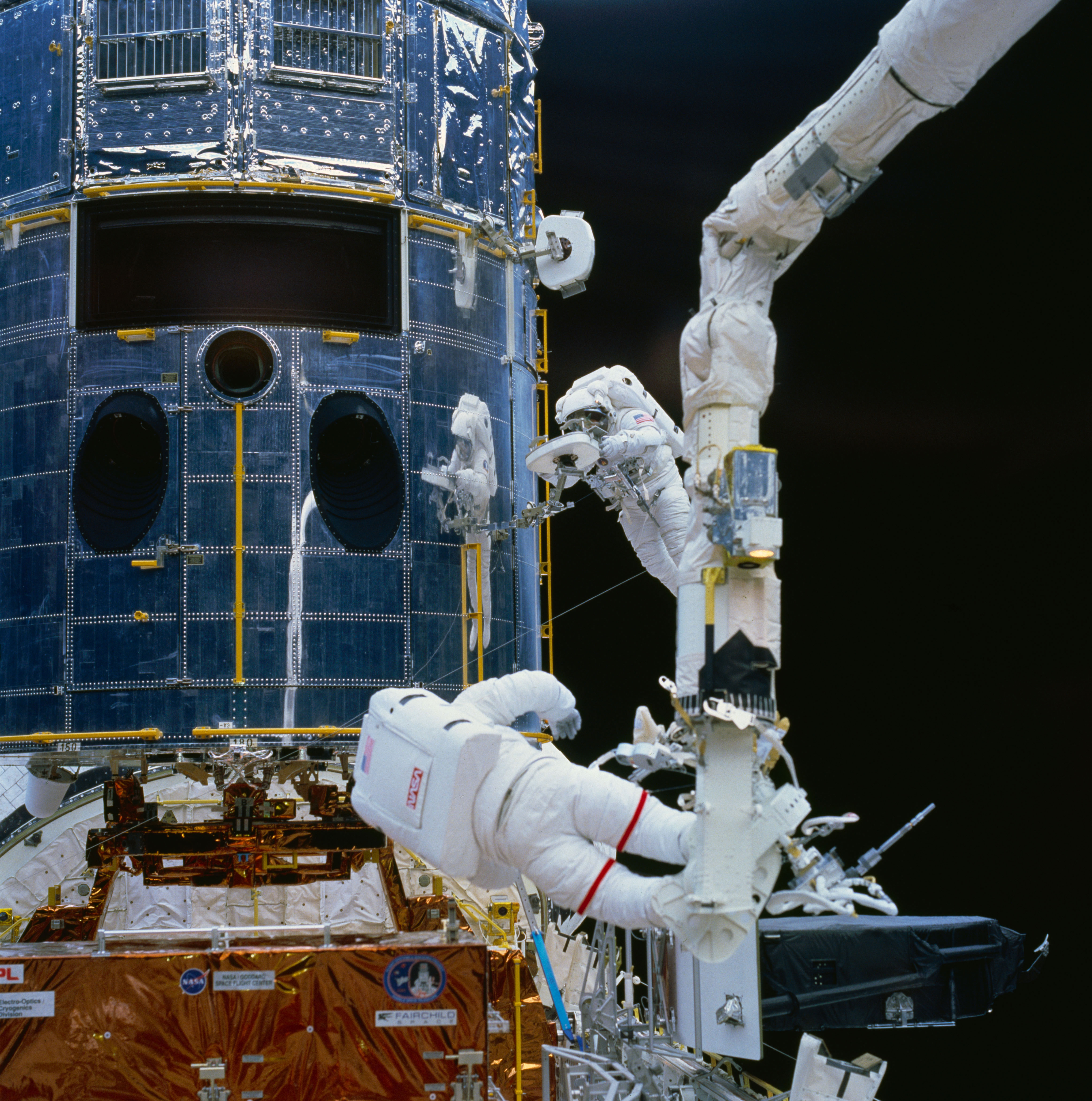 Astronaut Story Musgrave (top right center) works with a restraint device near the Hubble Space Telescope during the first of five STS-61 EVAs. Fellow NASA astronaut Jeffrey Hoffman is seen at the bottom of the frame preparing to work with fuse plugs. Credit: NASA