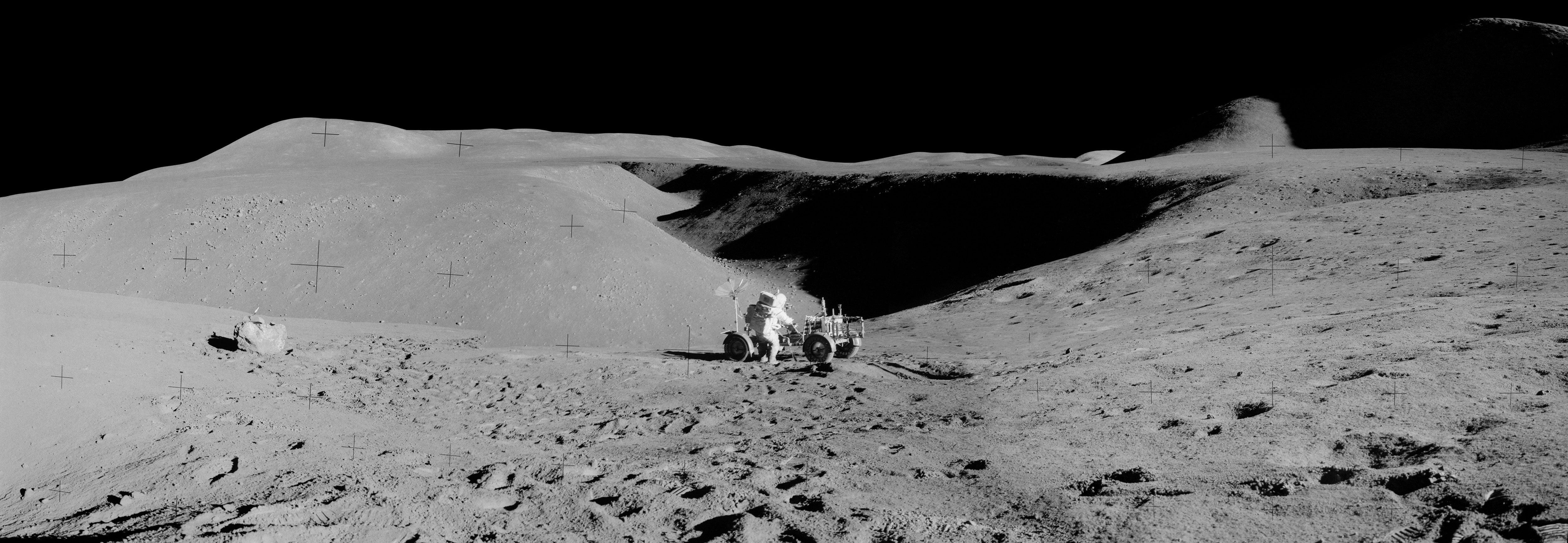Apollo 15 astronaut Dave Scott and the Lunar Rover with a view up Hadley Rille in the background. Credit: NASA via Retro Space Images