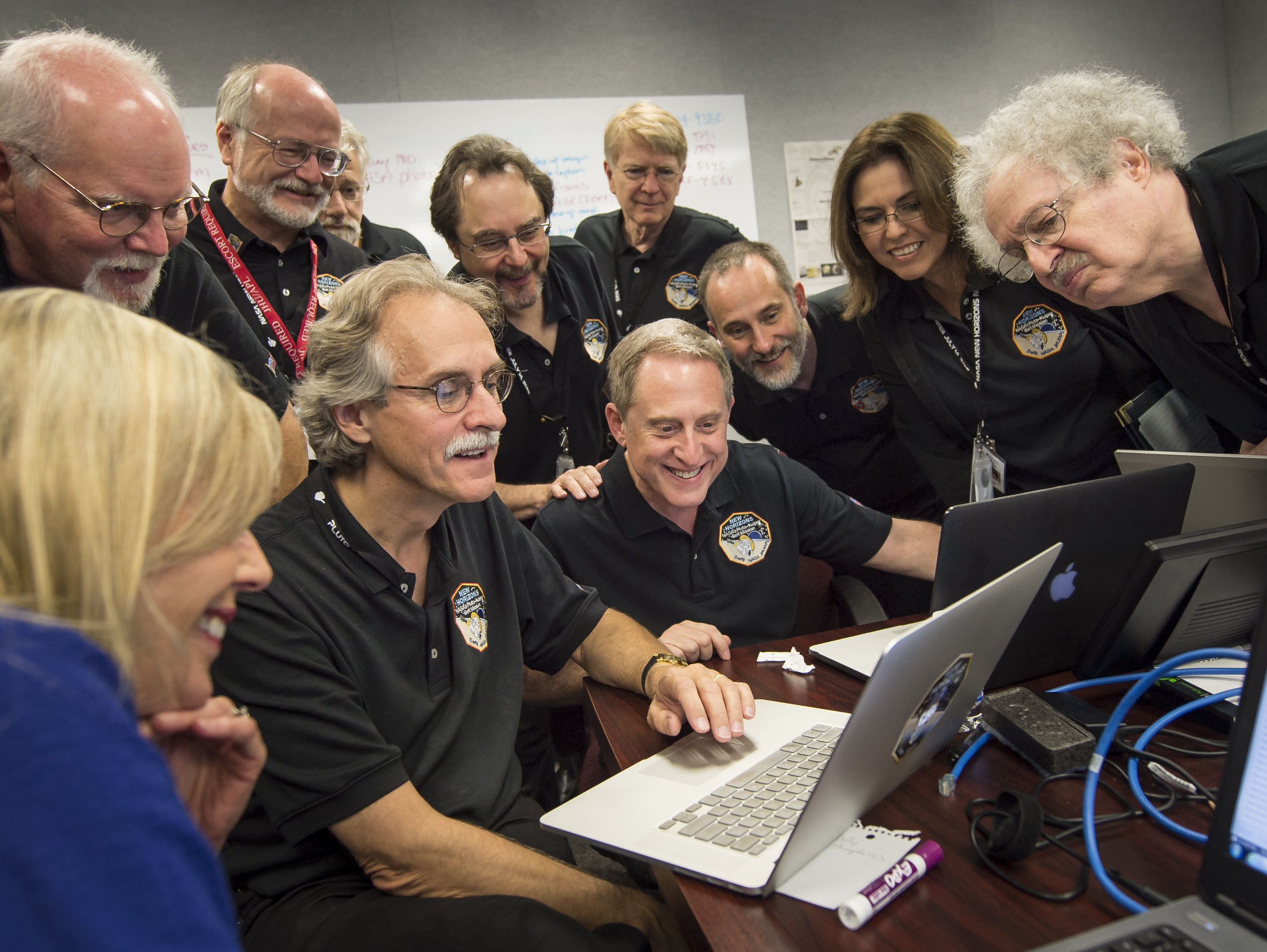 Members of the New Horizons team and embedded journalist, standing left, Jeff Moore, science team, NASA Ames Research Center; Randy Gladstone science team Southwest Research Institute (SwRI); Andy Chaikin, science writer; Willam Lewis, science writer; Will Grundy, science team, Lowell Observatory; Maria Stothoff, media relations, Johns Hopkins University Applied Physics Laboratory (APL); Steve Maran, science writer, seated; Laura Cantillo, NASA media relations, left, John Spencer, science team, Southwest Research Institute; and New Horizons Principal Investigator Alan Stern of SwRI gather around a laptop and smile as they review new processed images from the New Horizons spacecraft, Wednesday, July 15, 2015 at APL in Laurel, Md. Credit: NASA/Bill Ingalls