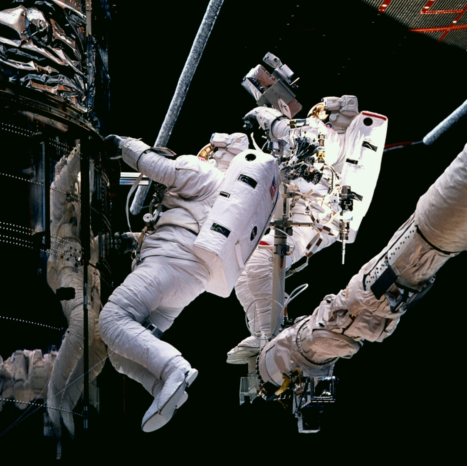 Payload Commander Mark C. Lee (left) and Mission Specialist Steven L. Smith (on RMS arm) conducting an unscheduled fifth extravehicular activity (EVA) during which they attach several thermal insulation blankets to three of Hubble's equipment compartments at the top of the Support Systems Module section. Credit: NASA