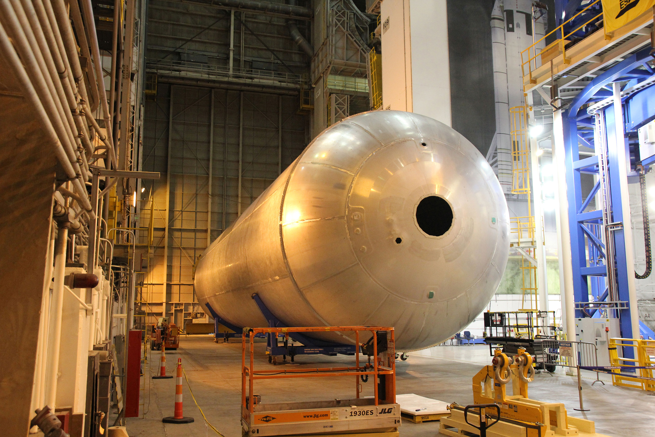 The newly assembled first liquid hydrogen tank, also called the qualification test article, for NASA's new Space Launch System rocket lies horizontally beside the Vertical Assembly Center robotic weld machine (blue) on July 22, 2016. It was lifted out of the welder after final welding was completed at NASA's Michoud Assembly Facility in New Orleans. Credit: Ken Kremer